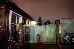 Ockupanterna har ställt upp plåt för att skydda Hemlösas hus mot lagens långa arm. Hittills har polisen hållit låg profil.