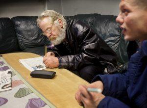 Thomas Larson löser korsord i tevesoffan på Hemlösas husoch planerar förännu en övernattning. Fredrik Bergesen, närmast,har erbjudits plats på Fenix, men vägrar. Hanvill hellre till Carnot, ett stödboende med generösare regelverk.