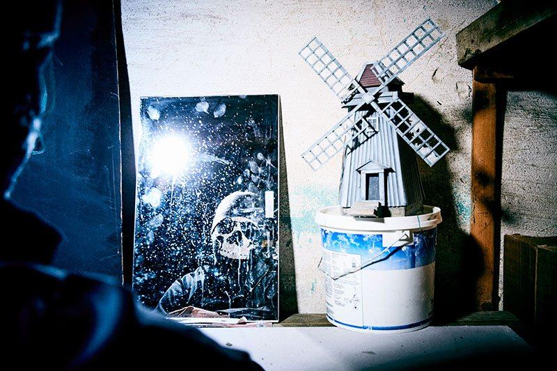 Ett fönsterlöst förråd i källaren på Roffes hyreshus tjänstgör även som hans ateljé. Väderkvarnen limmade han ihop av papp för att ha som modell till en affisch han ritade. Men pappskulpturen syns även flimra förbi i youtubevideon där Roffe tillkännager sin återkomst.
